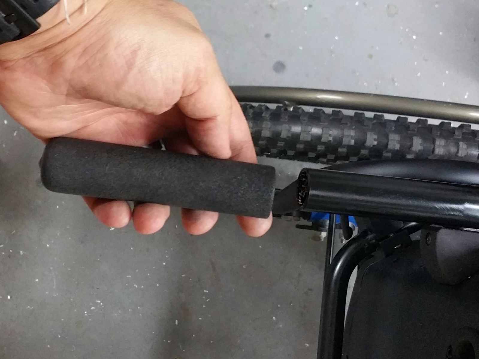 image of a hand removing standard sized wheelchair handle grip