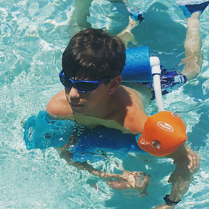 image of boy swimming with adapated swim float